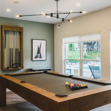 Billiards table and arcade game in clubroom overlooking outdoor pool
