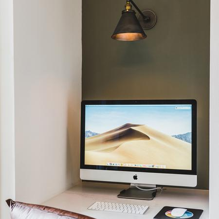 Built-in desk with Mac desktop computer and leather chair in small nook
