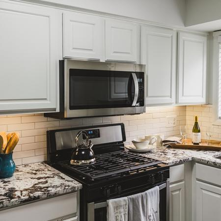 Upgraded kitchen with new appliances, granite counters, white cabinets and subway tile backsplash