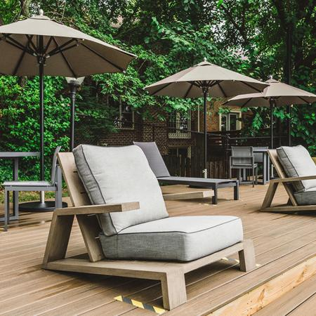 Sundeck in pool area with new patio chairs, umbrellas and tables