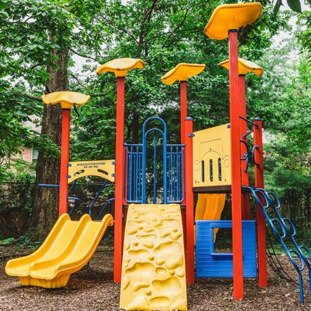 On site children's playscape with slides and climbing features