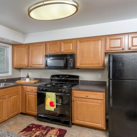 Classic kitchen with black appliances, oak cabinets and tile floors