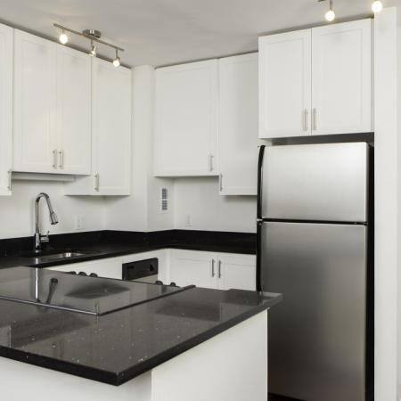 Black granite counters, stainless appliances in modern kitchen