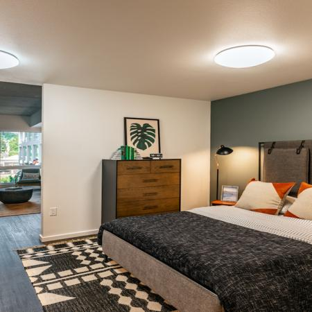 Open bedroom space with large queen sized bed and dresser area