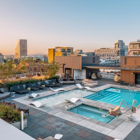 Dramatic pool with chaise lounge seating, private cabanas and stunning Portland views