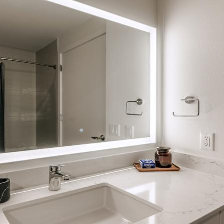 Spa inspired bathrooms with quartz marble countertops and backlit mirror
