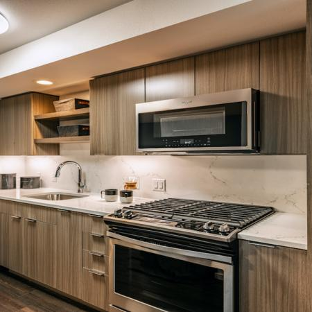Kitchen with warm chestnut cabinetry, gas cooking and stainless steel appliances