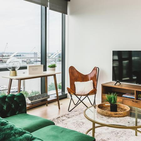 Living room with green velvet sofa, TV, and views of the Anacostia River