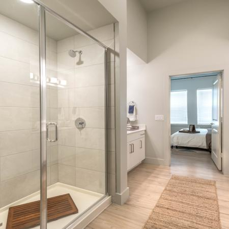 Brightly Lit Bathroom with Tile Surround Shower
