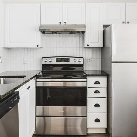Brightly lit reimagined kitchen with dark granite countertops, stainless appliances, and light cabinetry