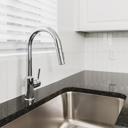 Close up on chrome kitchen spray nozzle with window above