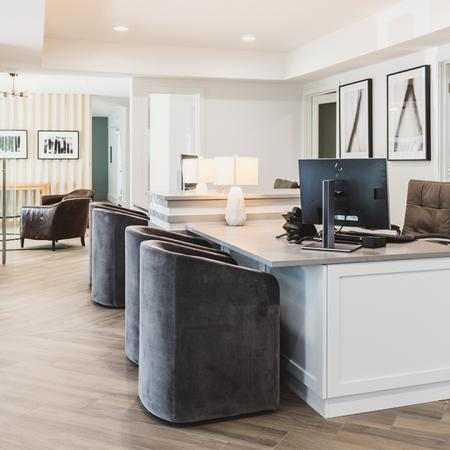 Brighty lit leasing office with desk and guest chairs