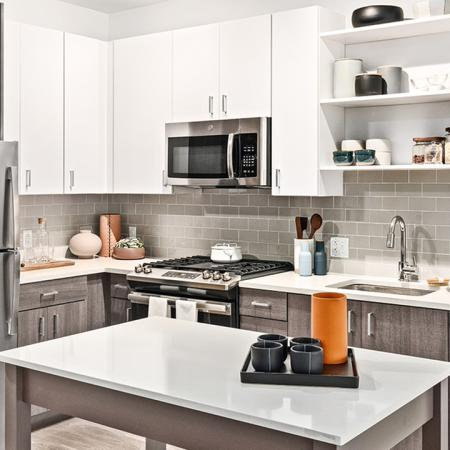 Beautifully equipped kitchens with stunning white cabinetry with chrome pulls and stainless steel appliances