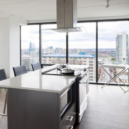 Kitchen with glass cook top in an island with floor to ceiling windows in the background