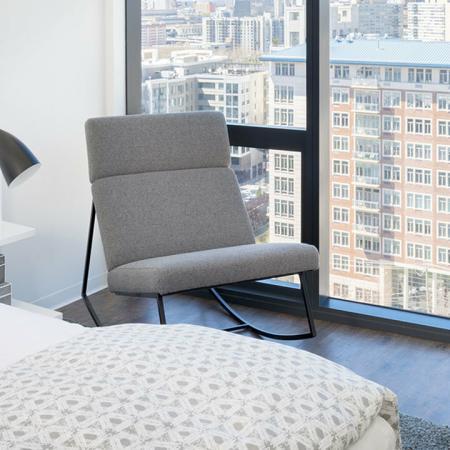 Chair in the corner of bedroom next to floor to ceiling windows