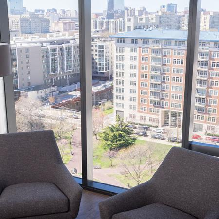 Living room in high rise with floor to ceiling windows and two chairs  near windows