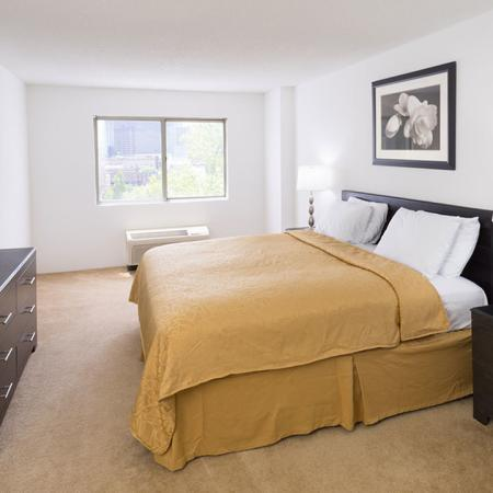 Bedroom with queen bed, armoire and side table