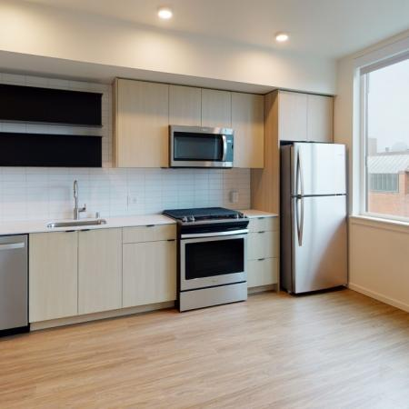 Galley Kitchen with view into living room in a Modera Broadway apartment.