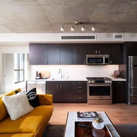 Stylish home with espresso cabinetry, stainless steel appliances complete with fun yellow and warm toned furnitureat Modera Rincon Hill apartments.