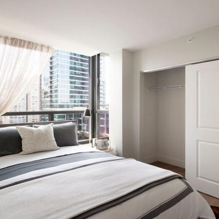 Large bedroom with sliding closets and built-in shelving at Modera Rincon Hill apartments.