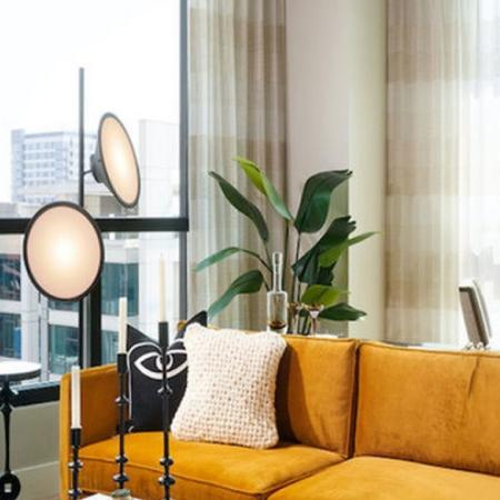 Luxe sofa and dining area with views of downtown San Francisco at Modera Rincon Hill apartments.