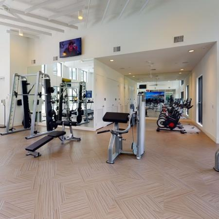 Expansive fitness center with spin bikes and weight stations with squat rack lifting area