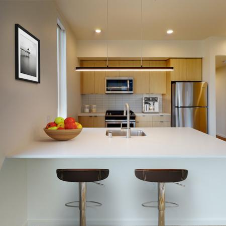 Beautiful kitchens with custom wood cabinetry and stainless steel appliances at Modera Broadway Apartments in Seattle.