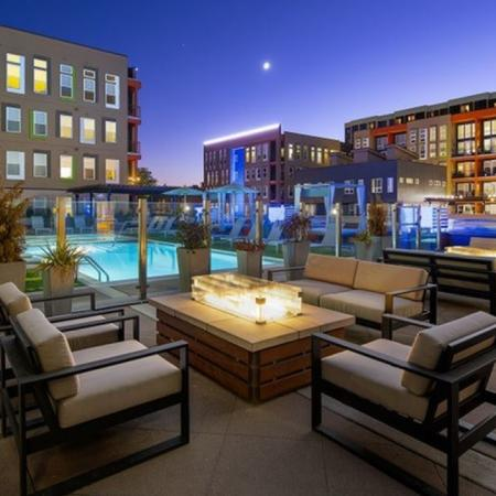 Outdoor firepit and chairs on pool deck at night