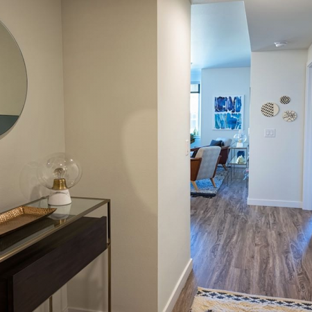 Hallway with console table and round mirror and hardwood floors