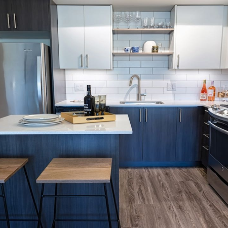 Kitchen with island, stainless appliances and bi-color cabinets