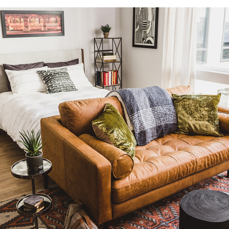 Spacious studio apartments in Atlanta with chic brown leather sofa and queen sized bed