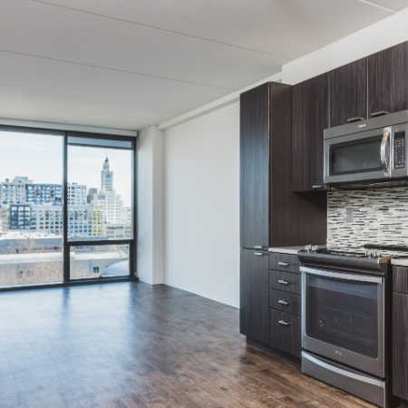 Kitchen with dark cabinetry open to living area