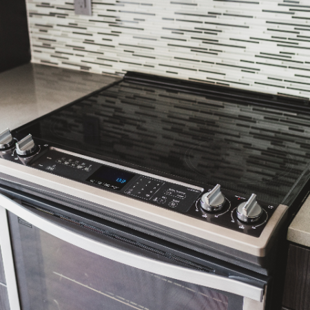 Close up of glass cook top and glass tiled backsplash