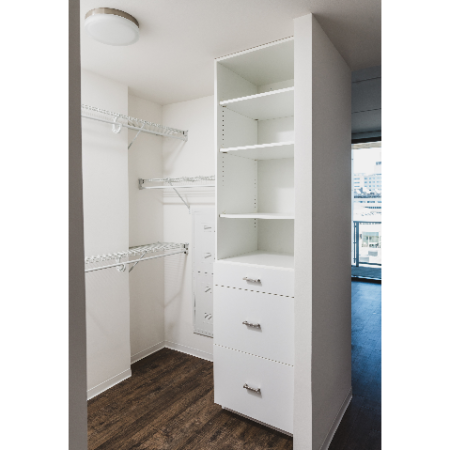 Walk in closet with custom cabinetry and drawers