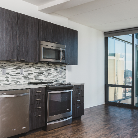 Open kitchen and dining area with floor to ceiling windows in the background