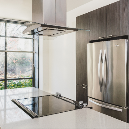 Kitchen with double sided, stainless steel refridgerator