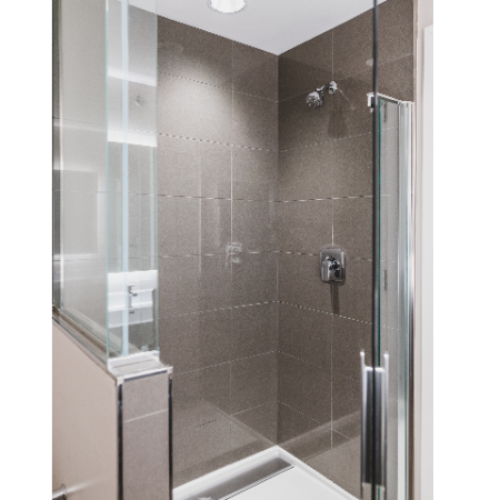 Glass enclosed shower with tile surround