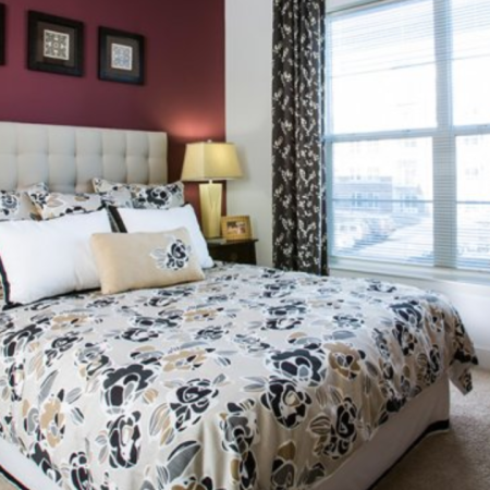 Bedroom with cream headboard bed and floral sheets