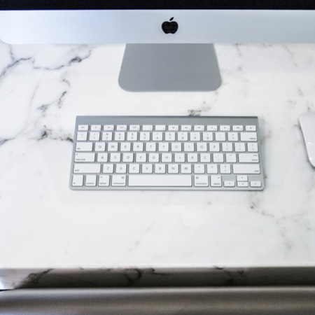 Mac desktop computer, keyboard, and mouse on marble counter