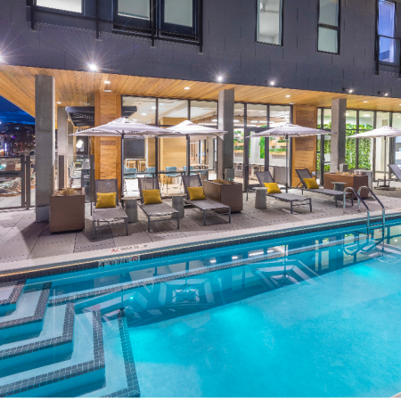 Elevated all-seasons resort-style pool with steps to enter the pool, lounge seating, umbrellas, and a hot tub