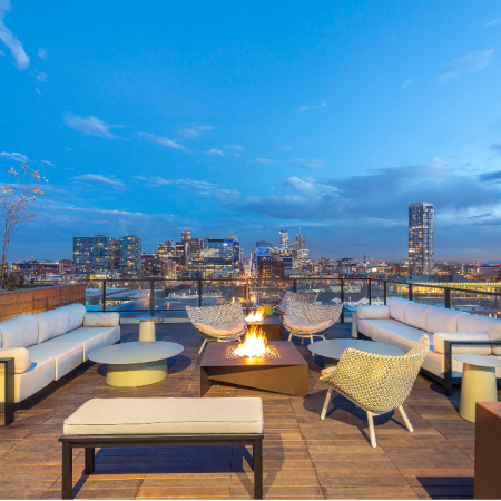 Rooftop terrace with a firepit, green spaces, and modern lounge seating facing stunning city views