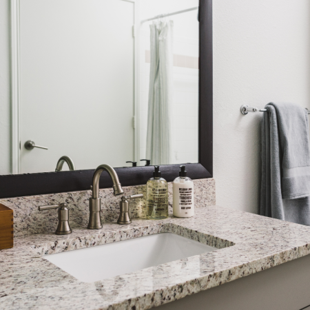 Bathroom with granite countertop and framed mirror