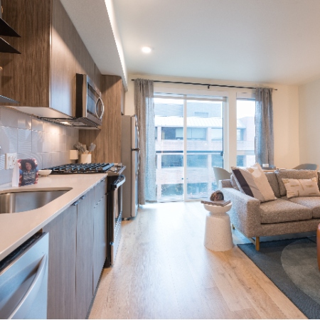 Modera Broadway kitchen featuring large windows, modern cabinetry, and a galley-style kitchen in Seattle apartments.