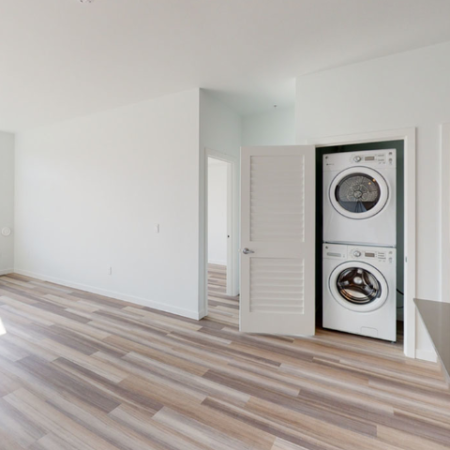 Washer and dryer in a closet in well-lit apartment with large windows