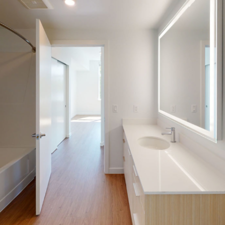 Spa-inspired bathrooms feature backlit mirrors and quartz counters