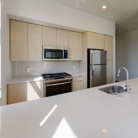 Light-filled kitchen, gas ranges, stainless steel appliances, and large windows