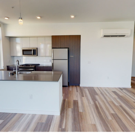 Open kitchen with high ceilings, modern cabinetry and large kitchen counter