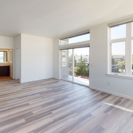 Large open windows and plank-style flooring with patio in the background