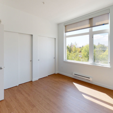 Bedroom featuring large oversized windows with roller shades