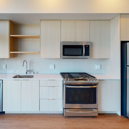 Lighter color scheme kitchen with abundant natural light and stainless steel appliances with a gas range